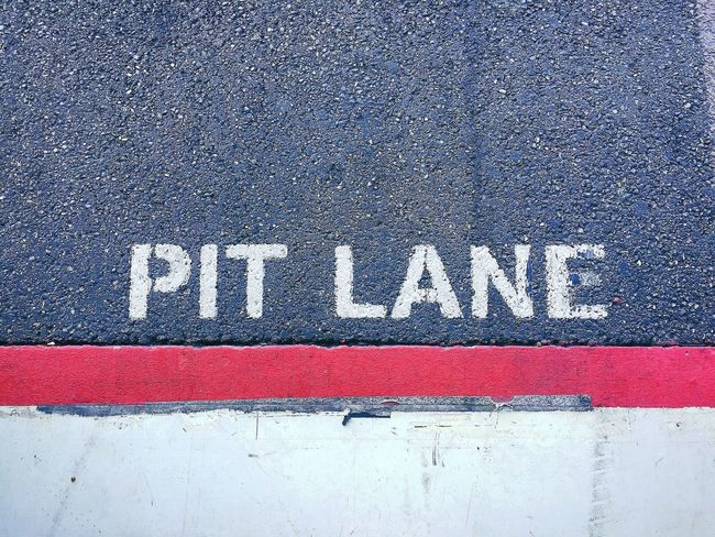 In the pitlane Red Textured  Communication Text No People Close-up Paint Outdoors White Color Day Concrete Pitlane Pit Lane Asphalt Asphaltography Asphalt Road Detail Road Street Graphism Asphalt Pavement