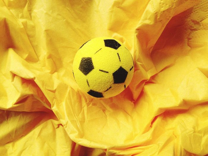 Close-up of soccer ball on yellow crumpled paper