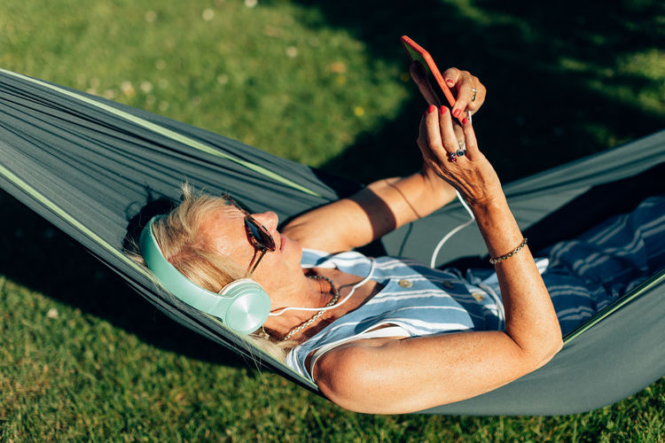 Caucasian senior lady swings in the hammock listening to music with phone and headphones.