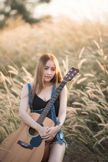 Acoustic Guitar Beautiful Woman Casual Clothing Field Front View Guitar Hair Hairstyle Holding Land Leisure Activity Lifestyles Music Musical Equipment Musical Instrument Nature One Person Outdoors Plucking An Instrument Portrait Real People String Instrument Young Adult Young Women