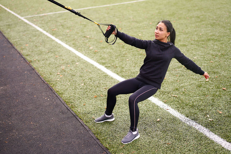 Full length of woman exercising on field