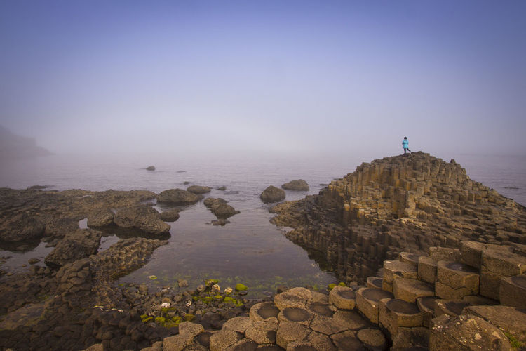 Mid distance view of woman standing on rocks by sea against sky during foggy weather