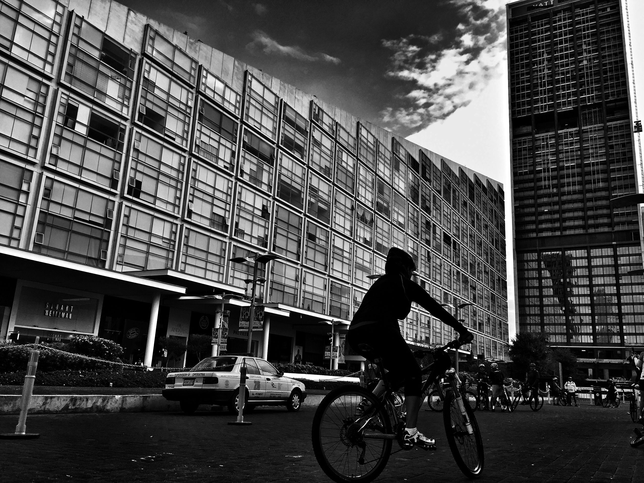 architecture, transportation, bicycle, built structure, building exterior, mode of transport, full length, city, men, on the move, land vehicle, riding, city life, leisure activity, cycling, sky, lifestyles, travel, office building, outdoors, cloud - sky, day, tall - high