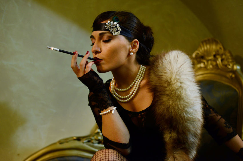 A woman smoking a cigarette . participant of Tbilisi City Celebration. 20s Actress Beauty Cigarette  Cigarette Holder Fur Glamour Indoors  Jazz Age Jewelry Make-up Only Women People Smoking Style Style And Fashion Young Women Women Around The World