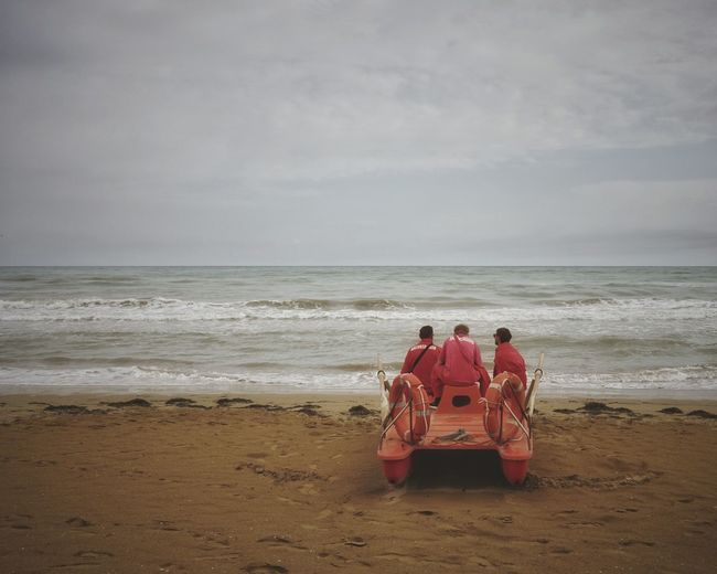 Men sitting on lifeboat at beach against sky