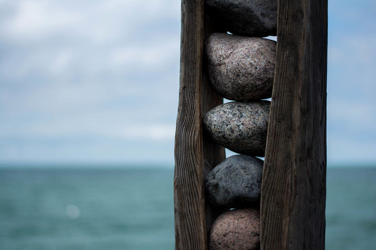 Close-up of stones amidst wood against sea