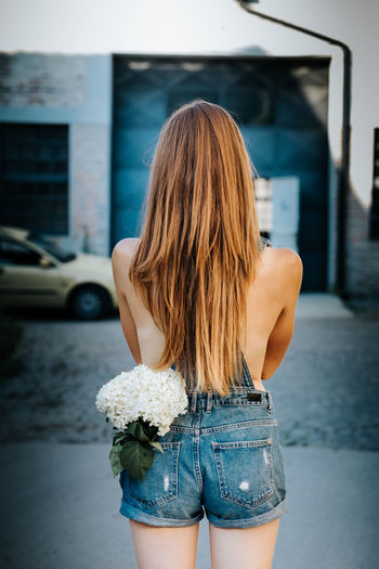 Anonymous female model with white flowers from back Anonymous Back Hot Plant Summertime Beautiful Woman Casual Clothing Day Fitness Flowers Hair Hairstyle Jeans Leisure Activity Lifestyles Long Hair One Person Outdoors Sexygirl Shorts Standing Summer Three Quarter Length Women Young Women