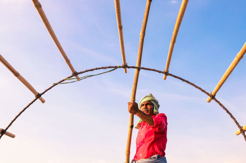 Low angle view of fisherman standing against sky during sunset