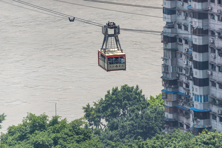 High angle view of overhead cable car over trees by buildings in city