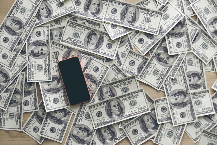 High angle view of mobile phone with paper currencies on table