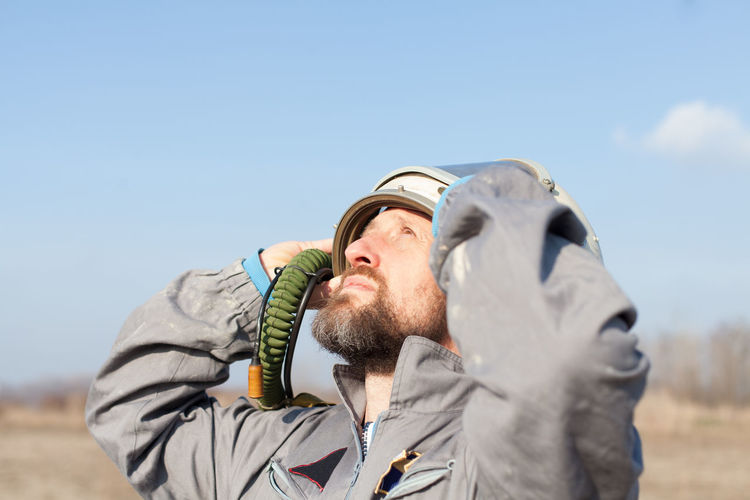 Close-Up Of Man Looking Up Against Sky