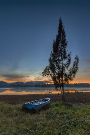 fragile boat in lake cileunca, Pangalengan Bandung Bandung INDONESIA Beauty In Nature Field Grass Land Mode Of Transportation Moored Nature Nautical Vessel No People Non-urban Scene Outdoors Pangalengan Plant Rowboat Scenics - Nature Sky Sunset Tranquil Scene Tranquility Transportation Tree Water