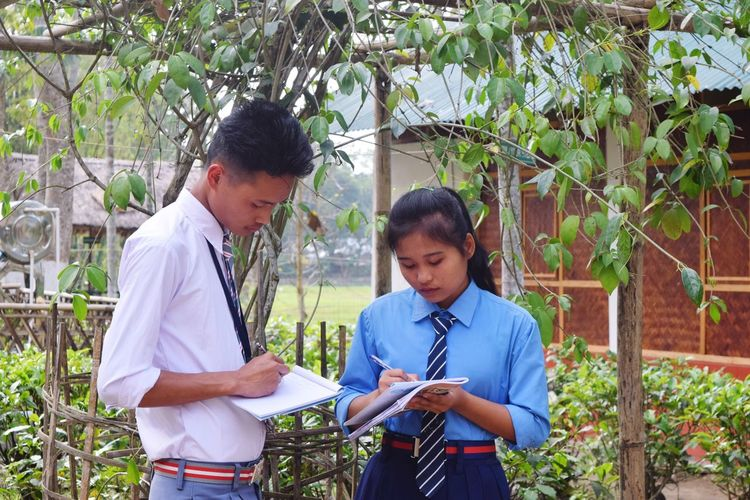 Teenage Girl With Friend Wearing School Uniforms Writing On Book