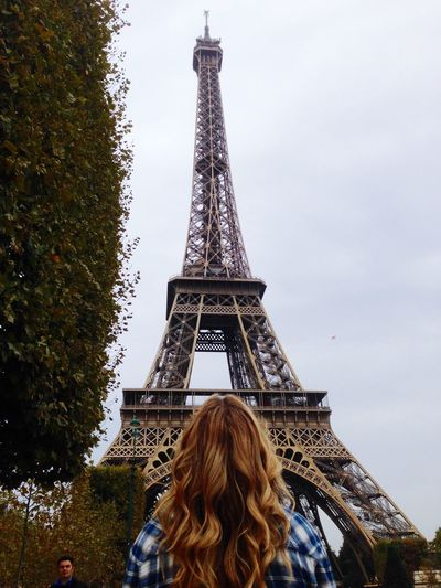 Rear view of woman standing in front of eiffel tower against sky
