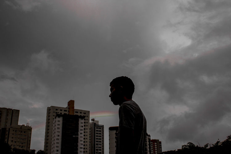 Low angle view of man looking at city against sky