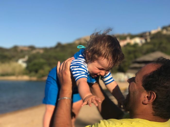 Close-up of happy father holding cute baby boy at beach