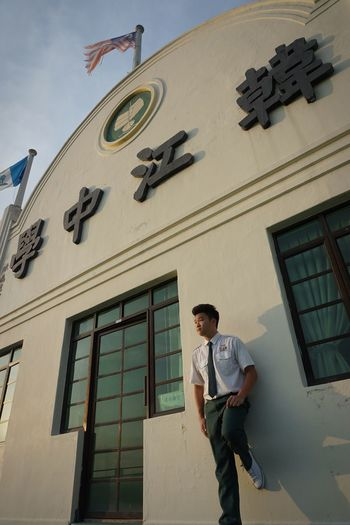 Low Angle View Of Teenage Boy Standing By School Building
