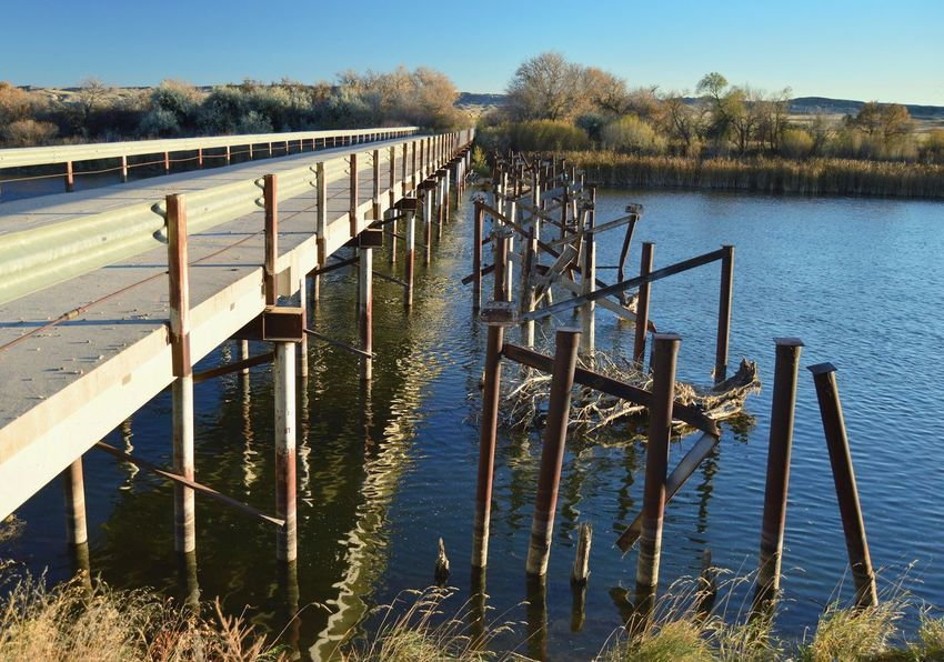 Rusty bridge girders Narrow Bridge Railing River Reflections In The Water Outdoors Late Evening South Of Orin Junction Wyoming Long Shadows Rusted Trees Facing South Water Sky Bridge - Man Made Structure