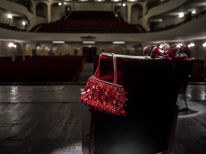 Purse and high heels on chair in auditorium