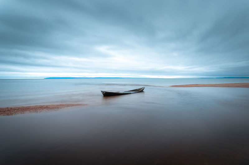 Lone boat with cloudy weather captured with long exposure