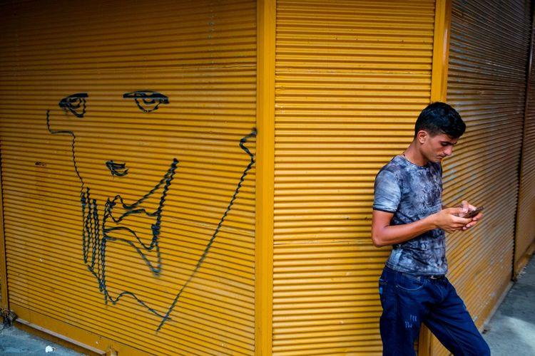 Full length of woman standing against graffiti wall