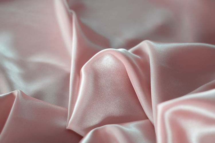 Silk Bed Sheet Pattern Indoors  Fragility Luxury Textile Folded Close-up Textured  Softness Satin Linen No People Crumpled Vulnerability  Backgrounds Wrinkled Full Frame Rippled Indoors  Selective Focus Furniture High Angle View Pink Color Vulnerability  White Color