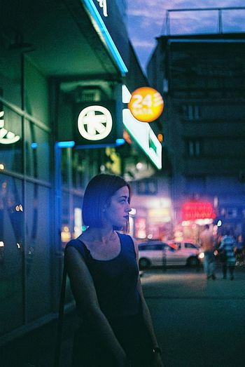 Woman standing on sidewalk against illuminated building in city at night