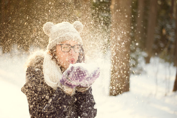 Adult Adults Only Cheerful Cold Temperature Day Enjoyment Fun Glove Happiness Motion Nature One Person One Woman Only One Young Woman Only Only Women Outdoors People Snow Snowflake Snowing Spraying Warm Clothing Winter Women Young Adult
