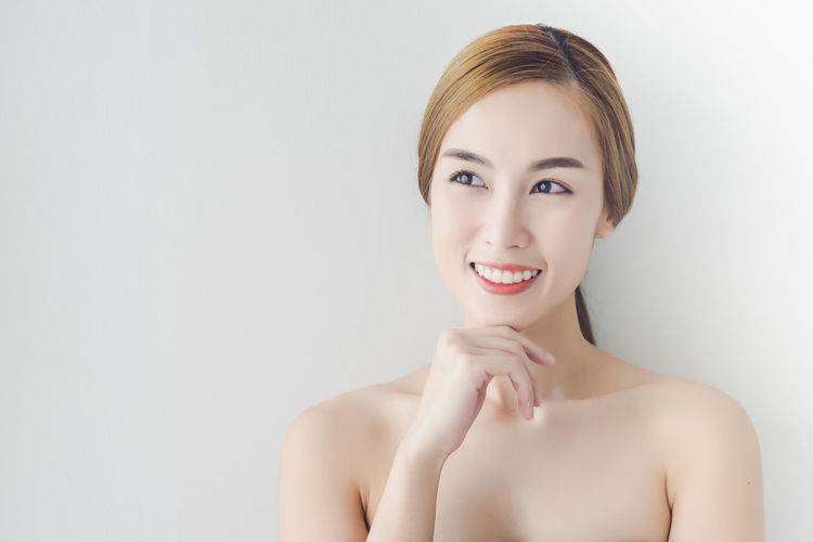 Thoughtful Young Woman Smiling Over White Background