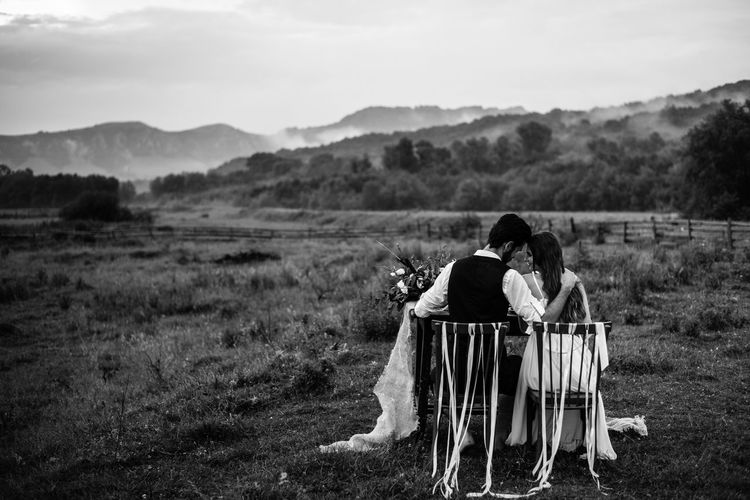 Rear View Of Newlywed Couple Sitting On Chairs Against Mountains