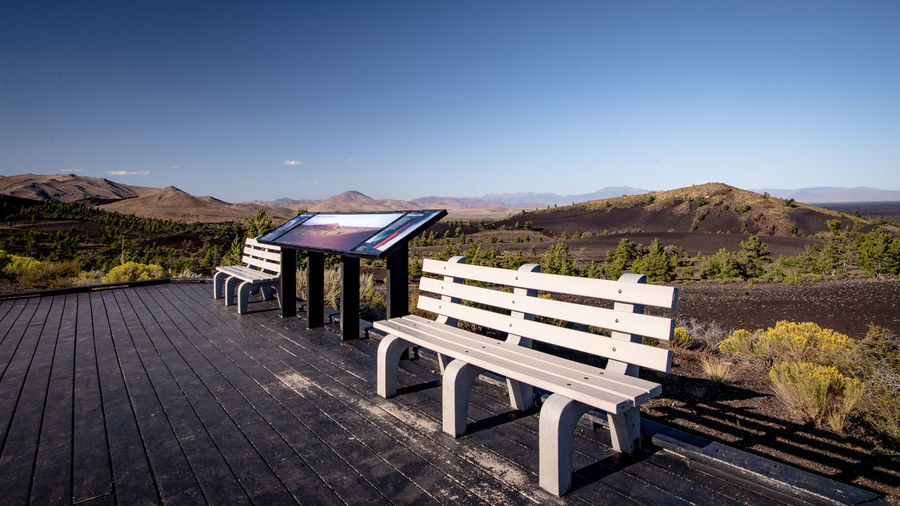 Empty bench on hill against clear blue sky
