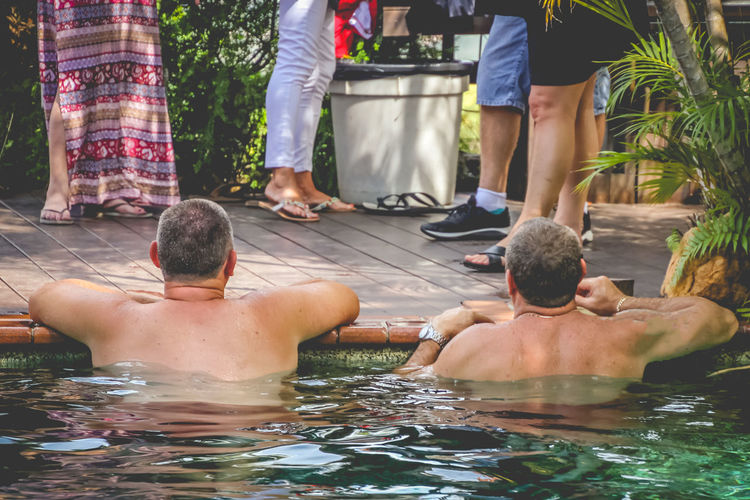 Shirtless man looking people at party