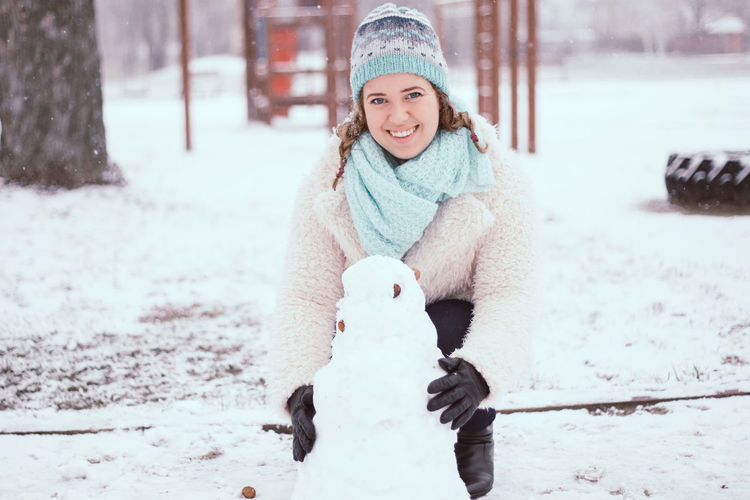 Portrait Of Smiling Young Woman Making Snowman At Park During Winter