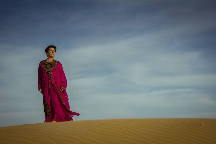 Low angle view of woman standing at desert against sky