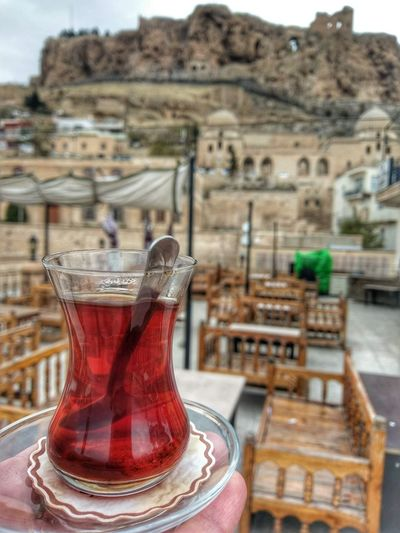 Close-up of drink on table against buildings in city
