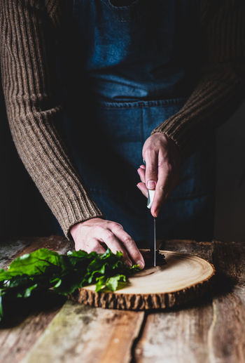 Midsection of woman having food on cutting board