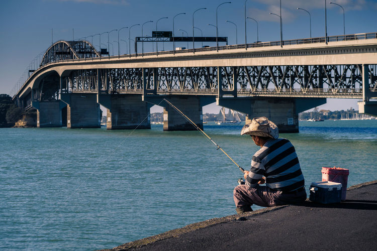 Preparing for fish and chips Auckland Harbour Bridge Waitemata Harbour Architecture Bridge Bridge - Man Made Structure Built Structure Casual Clothing Connection Day Fishing Leisure Activity Lifestyles Men Nature One Person Outdoors Real People Sitting Sky Transportation Water