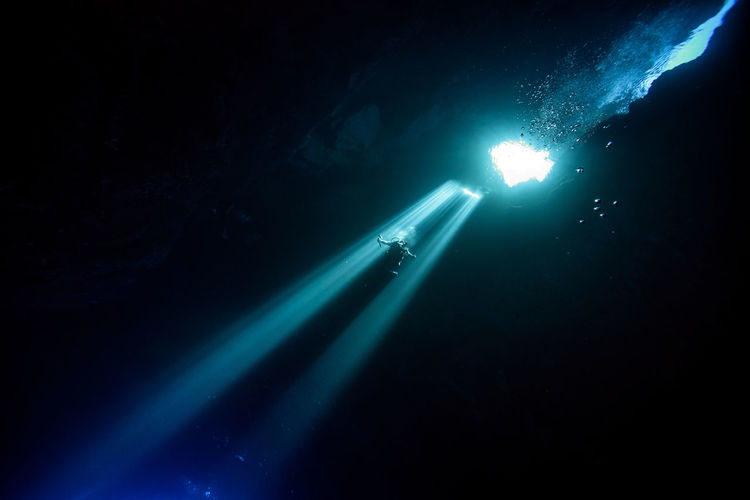 Low angle view of sunlight falling on silhouette person scuba diving undersea