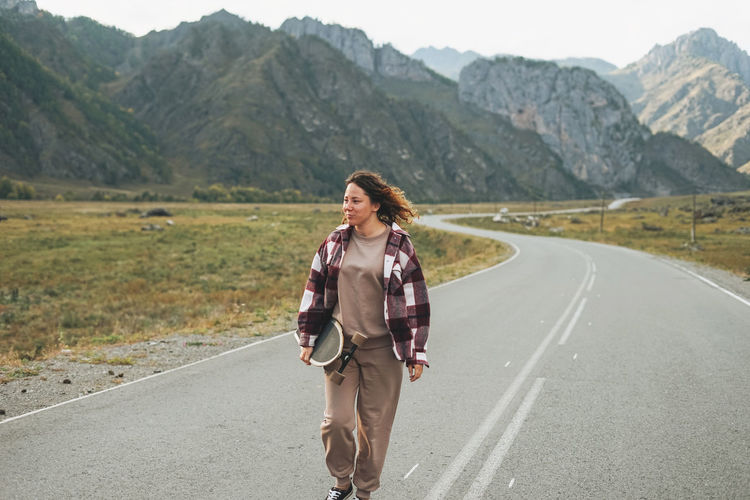 Young woman on skateboard on road against the beautiful mountain landscape, chemalskiy tract, altai