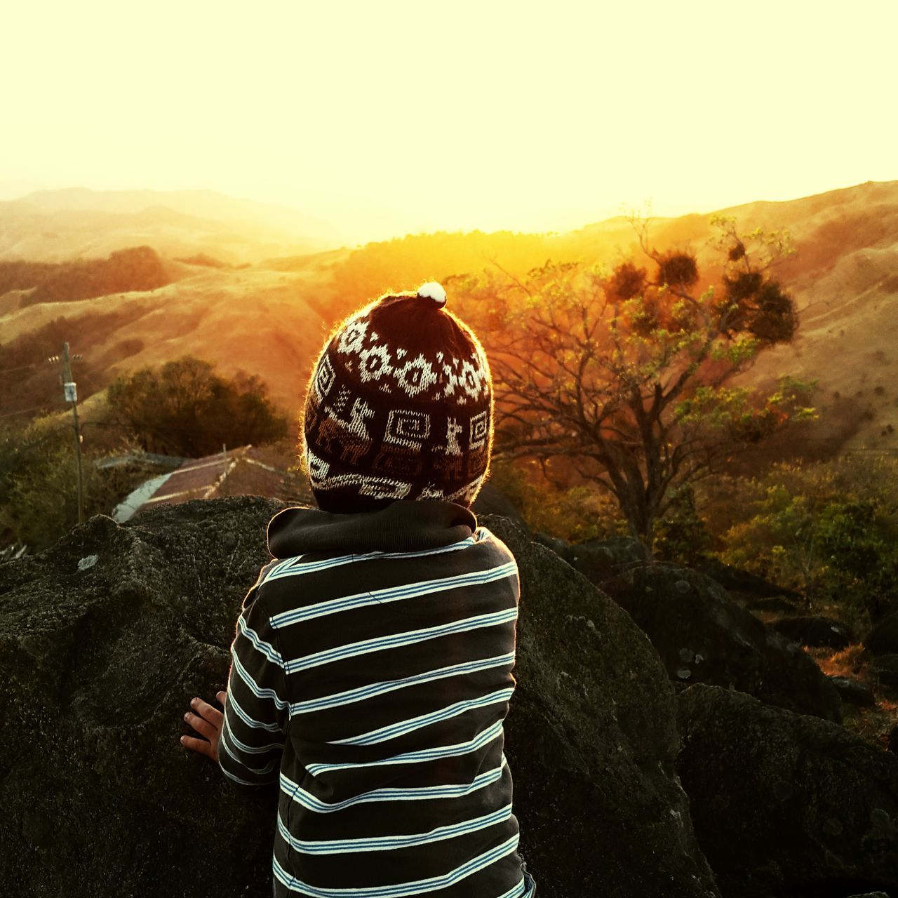 rear view, real people, striped, childhood, standing, boys, one person, casual clothing, outdoors, rock - object, nature, leisure activity, field, day, lifestyles, landscape, mountain, one boy only, tree, beauty in nature, sky, people