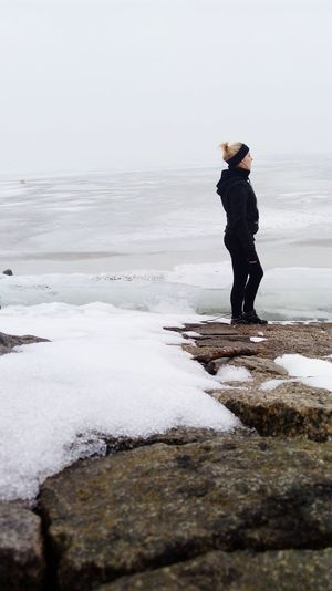 Side View Of Woman Standing On Rock Formation By Frozen Lake Against Sky During Winter