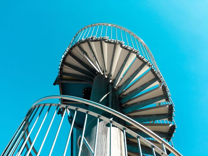 Low angle view of staircase against clear blue sky