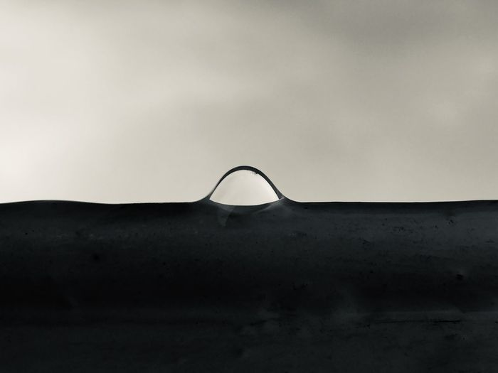 Low angle view of metallic structure against wall