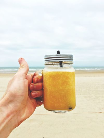 Cropped Image Of Hand Holding Drink In Mason Jar At Beach Against Sky