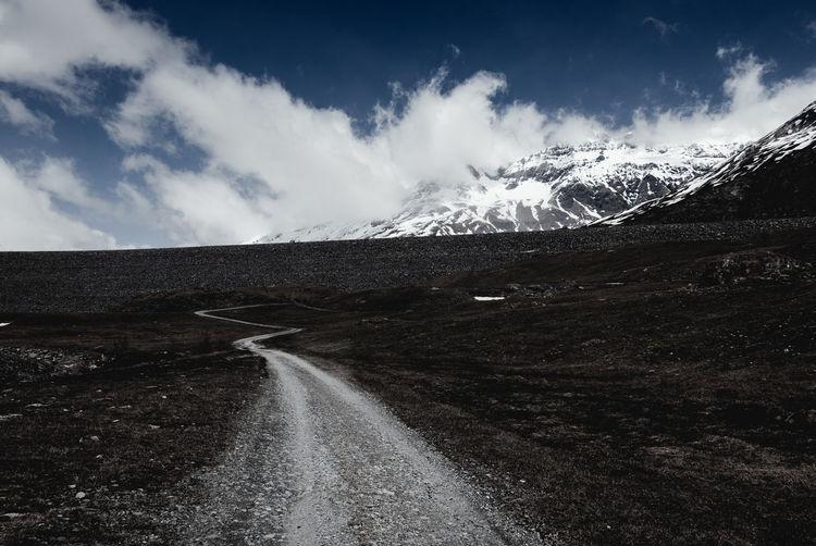 Empty road amidst landscape leading towards snowcapped mountains