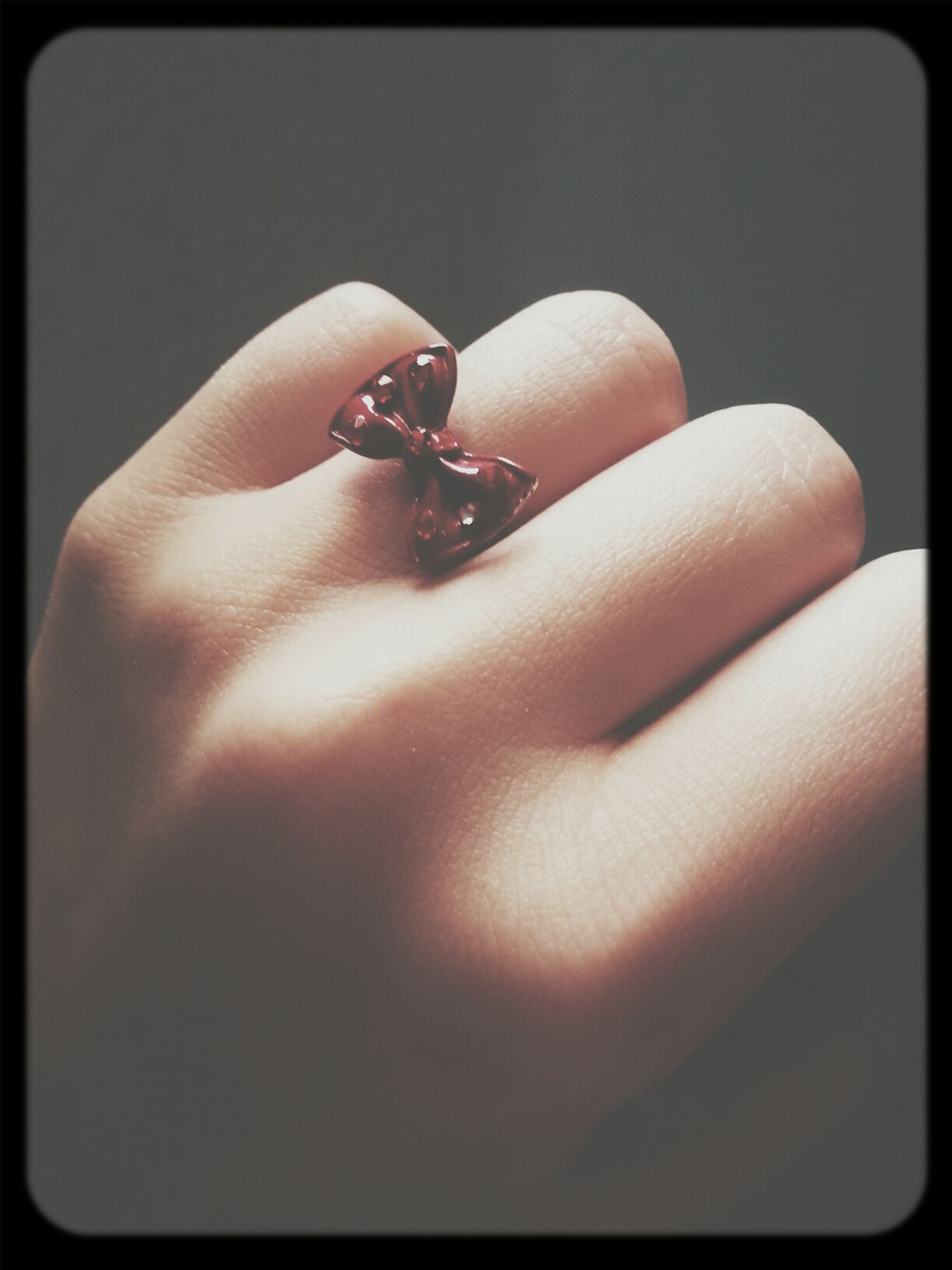transfer print, person, auto post production filter, indoors, close-up, part of, human finger, holding, lifestyles, cropped, studio shot, femininity, red, leisure activity, fashion, ring