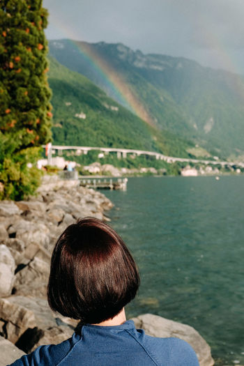 Rear view of woman by lake against mountains and sky