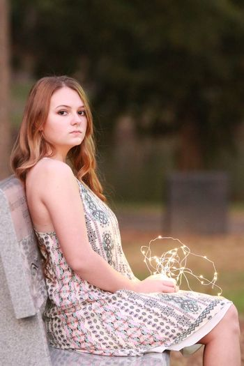 Portrait Of Beautiful Woman Holding Illuminated String Lights While Sitting On Bench
