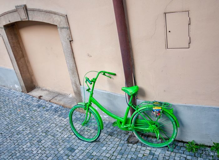 Bicycle leaning against wall of building