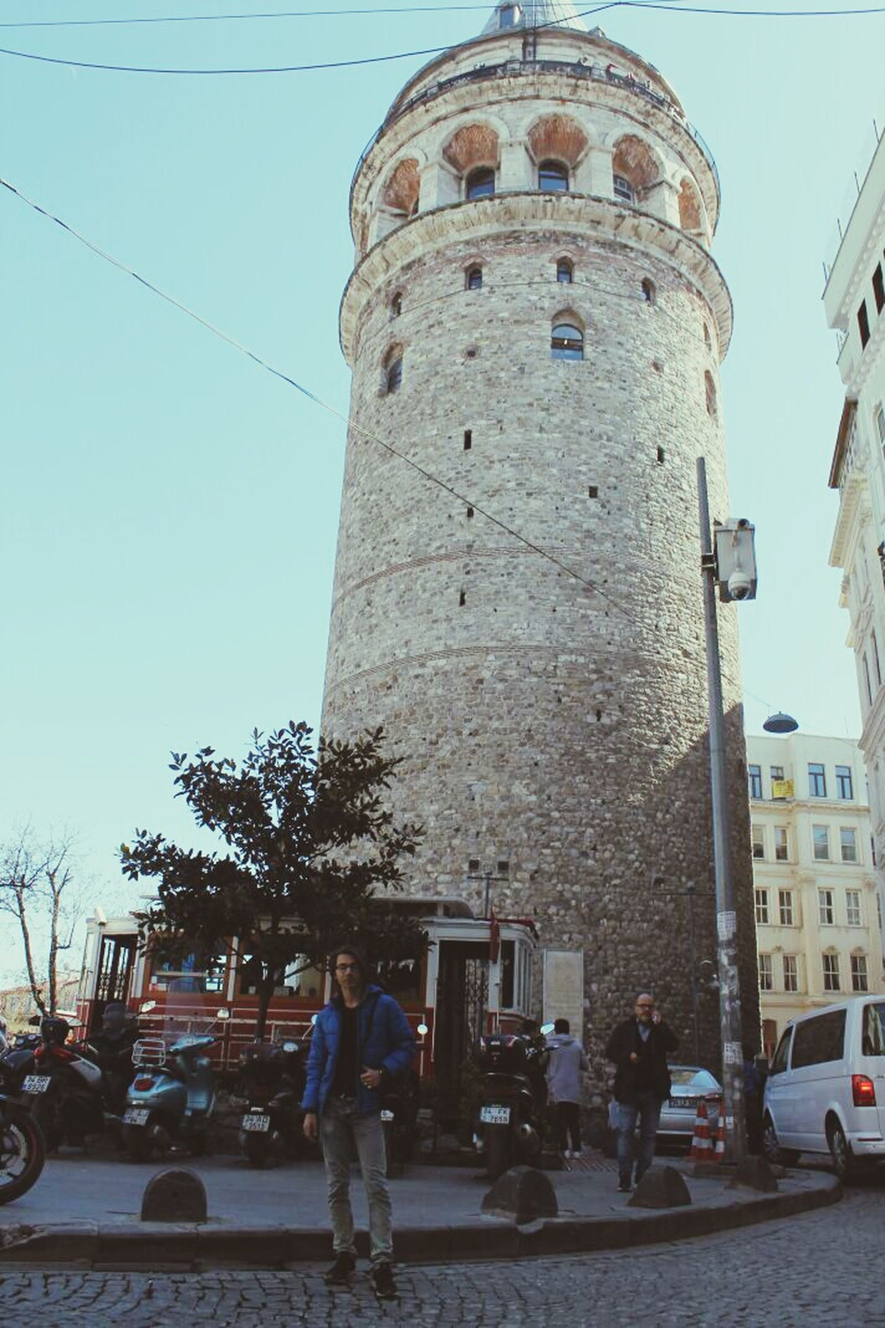 city, tower, built structure, architecture, car, outdoors, travel destinations, day, sky, adults only, real people, people, adult, one person